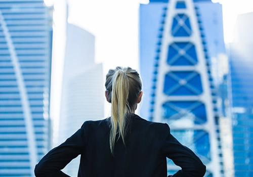 高層ビルを見上げる女性
