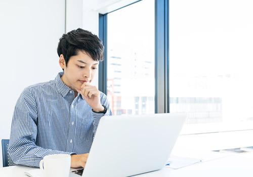 パソコンを見ながら考える男性